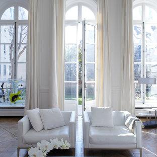 Cette image montre un grand salon design ouvert avec une salle de réception, un mur blanc, un sol en bois brun, aucune cheminée et aucun téléviseur.
