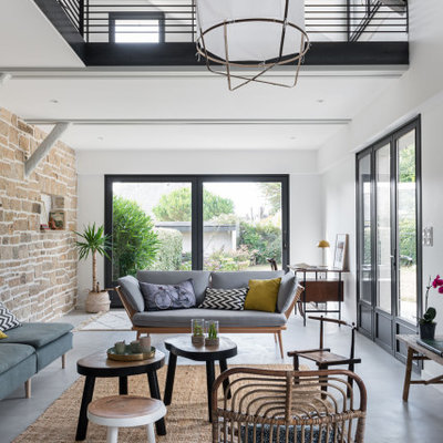 Example of a large danish open concept gray floor living room design in Nantes with white walls