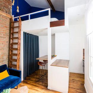 Aménagement d'un salon mansardé ou avec mezzanine industriel avec un mur blanc, un sol en bois brun et un sol marron.