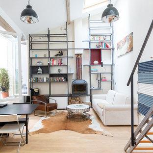 Cette image montre un grand salon avec une bibliothèque ou un coin lecture urbain ouvert avec un mur blanc, un sol en bois clair, un poêle à bois et aucun téléviseur.
