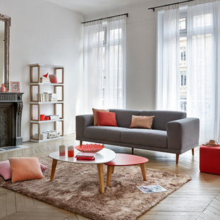 Cette image montre un grand salon design ouvert avec un mur blanc, un sol en bois clair, une cheminée standard, un manteau de cheminée en pierre et aucun téléviseur.
