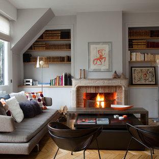Idée de décoration pour un salon avec une bibliothèque ou un coin lecture champêtre de taille moyenne et fermé avec un mur gris, un sol en bois clair, une cheminée standard, un manteau de cheminée en brique et aucun téléviseur.