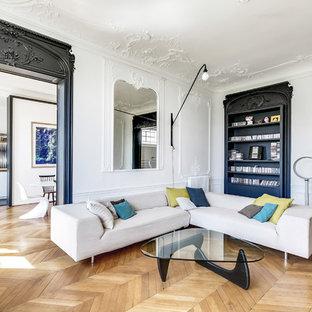 Réalisation d'un grand salon avec une bibliothèque ou un coin lecture tradition fermé avec un mur blanc, un sol en bois brun, aucune cheminée et aucun téléviseur.