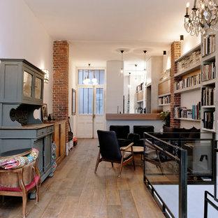Cette image montre un salon urbain de taille moyenne avec un mur blanc, un sol en bois brun, aucune cheminée et aucun téléviseur.