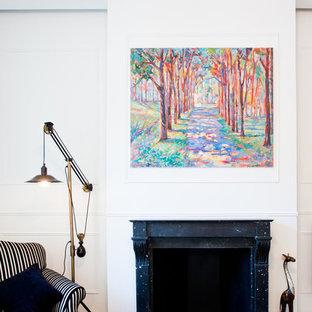 Exemple d'un salon tendance de taille moyenne et ouvert avec un mur blanc, un sol en bois clair, une cheminée standard, un manteau de cheminée en pierre et aucun téléviseur.