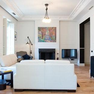 Aménagement d'un grand salon contemporain fermé avec une salle de réception, un mur blanc, un sol en bois brun, une cheminée standard, un téléviseur fixé au mur et un manteau de cheminée en pierre.