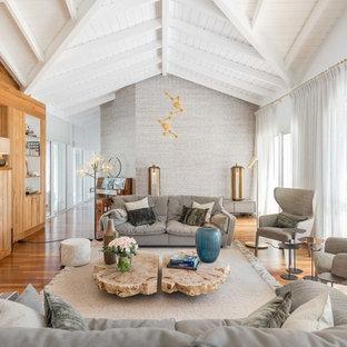 Aménagement d'un grand salon bord de mer avec un sol en bois brun, un sol marron, une salle de réception, un mur gris, une cheminée standard et un manteau de cheminée en bois.