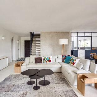 Aménagement d'un salon contemporain ouvert avec un mur blanc, aucune cheminée, aucun téléviseur et un sol blanc.
