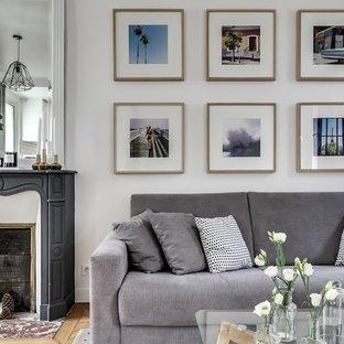 Foto de salón para visitas cerrado, escandinavo, de tamaño medio, sin televisor, con paredes blancas, suelo de madera clara y chimenea tradicional