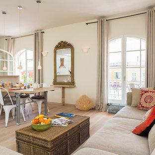 Idée de décoration pour un grand salon avec une bibliothèque ou un coin lecture design ouvert avec un mur beige, un sol en bois clair, aucune cheminée et aucun téléviseur.