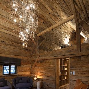 Cette image montre un salon chalet avec un mur marron, un sol en bois foncé et un sol marron.