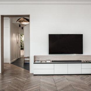 Esempio di un ampio soggiorno minimal aperto con sala della musica, pareti bianche, parquet chiaro e TV autoportante