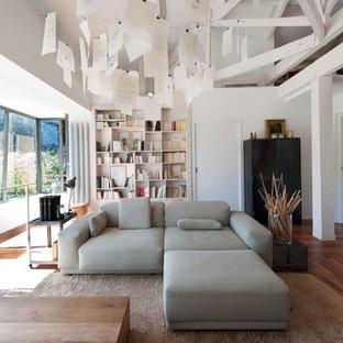 Inspiration pour un grand salon avec une bibliothèque ou un coin lecture design ouvert avec un mur blanc, un sol en bois foncé, aucune cheminée et aucun téléviseur.