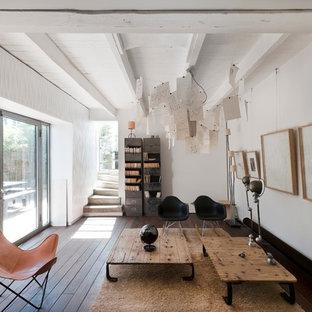 Cette image montre un grand salon avec une bibliothèque ou un coin lecture design fermé avec un mur blanc, un sol en bois foncé, aucune cheminée et aucun téléviseur.