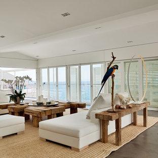Cette photo montre un grand salon bord de mer ouvert avec une salle de réception, un mur blanc, aucune cheminée et aucun téléviseur.