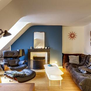 Cette photo montre un salon éclectique avec un mur bleu, un sol en bois brun, une cheminée standard et un sol marron.