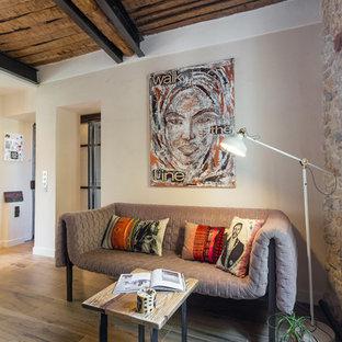 Cette photo montre un salon méditerranéen de taille moyenne et ouvert avec une salle de réception, un mur beige, un sol en bois clair, aucune cheminée et aucun téléviseur.