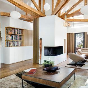 Cette photo montre un salon avec une bibliothèque ou un coin lecture tendance ouvert avec un mur blanc, un sol en bois brun, une cheminée d'angle, un téléviseur fixé au mur et un sol marron.