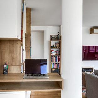 Foto de biblioteca en casa abierta, actual, grande, sin chimenea, con paredes blancas, suelo de contrachapado, televisor colgado en la pared y suelo beige