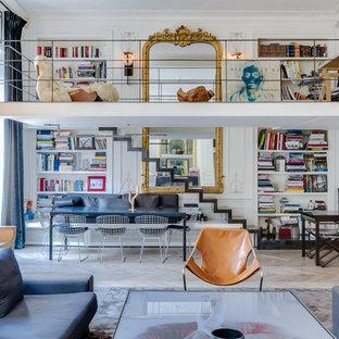 Exemple d'un salon avec une bibliothèque ou un coin lecture éclectique de taille moyenne et ouvert avec un mur blanc, un sol en bois clair, aucune cheminée et aucun téléviseur.