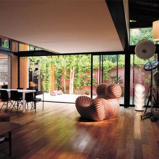 Aménagement d'un salon contemporain de taille moyenne et ouvert avec une salle de réception, un sol en bois foncé, un mur blanc, aucune cheminée et aucun téléviseur.