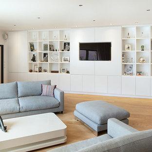 Exemple d'un grand salon avec une bibliothèque ou un coin lecture tendance fermé avec un mur blanc, un sol en bois brun, aucune cheminée et un téléviseur encastré.