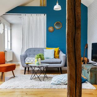 Exemple d'un salon éclectique fermé avec une salle de réception, un mur bleu, un sol en bois clair et un téléviseur indépendant.