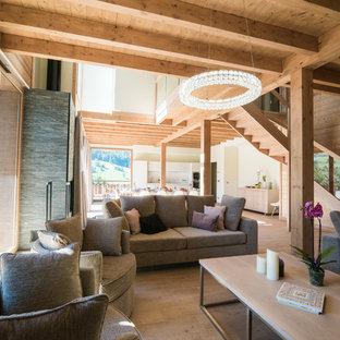 Cette photo montre un salon montagne ouvert avec un sol en bois clair, aucune cheminée et un sol beige.