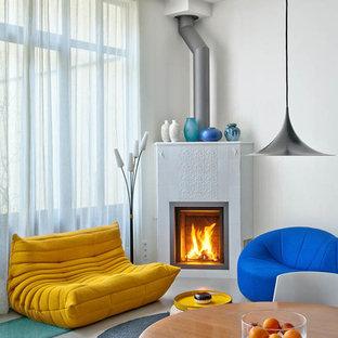 Ejemplo de salón abierto, moderno, de tamaño medio, sin televisor, con paredes azules, suelo de cemento, chimenea de esquina y marco de chimenea de baldosas y/o azulejos
