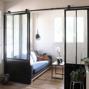 Foto di un piccolo soggiorno minimal chiuso con libreria, nessuna TV, pareti bianche, parquet chiaro, nessun camino e pavimento beige