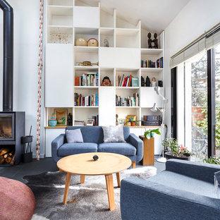 Idée de décoration pour un salon avec une bibliothèque ou un coin lecture nordique ouvert avec un mur blanc, un poêle à bois et un sol noir.