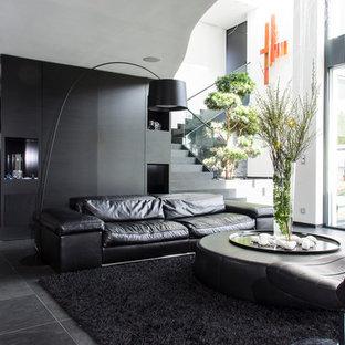 パリの大きいコンテンポラリースタイルのおしゃれなLDK (スレートの床、壁掛け型テレビ、黒い壁、暖炉なし) の写真