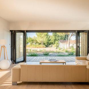 Cette image montre un salon minimaliste ouvert avec un mur blanc, un sol en bois brun et un sol marron.