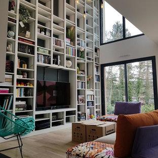Aménagement d'un salon avec une bibliothèque ou un coin lecture éclectique avec un mur blanc, un sol en bois clair, un téléviseur fixé au mur et un sol beige.