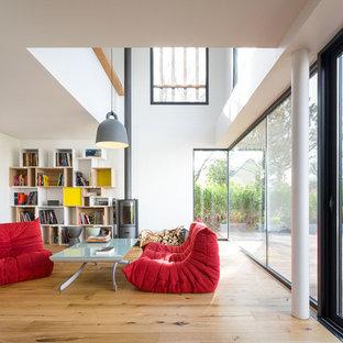Idée de décoration pour un grand salon avec une bibliothèque ou un coin lecture minimaliste ouvert avec un mur blanc, un sol en bois clair, un poêle à bois et aucun téléviseur.