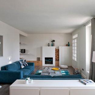 Réalisation d'un grand salon design fermé avec un mur blanc, un sol en bois foncé, une cheminée standard et aucun téléviseur.