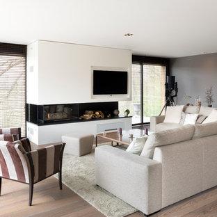 Idée de décoration pour un salon design de taille moyenne et ouvert avec une salle de réception, un mur gris, un sol en bois brun, une cheminée ribbon et un téléviseur fixé au mur.