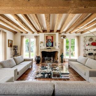 Cette image montre un grand salon rustique fermé avec un sol en carreau de terre cuite, un mur blanc, une cheminée standard, un manteau de cheminée en pierre, aucun téléviseur et une salle de réception.