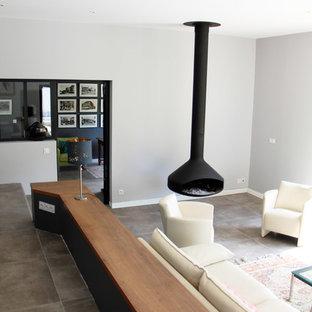 Immagine di un grande soggiorno minimal chiuso con sala formale, pareti bianche, pavimento in gres porcellanato, camino sospeso, cornice del camino in metallo, nessuna TV e pavimento grigio