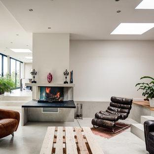 Cette image montre un très grand salon design ouvert avec béton au sol, une salle de réception, un mur blanc, un manteau de cheminée en béton, une cheminée standard et aucun téléviseur.