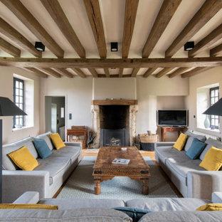 Cette photo montre un salon nature ouvert avec un mur beige, un sol en bois brun, une cheminée standard, un sol marron et un plafond en poutres apparentes.