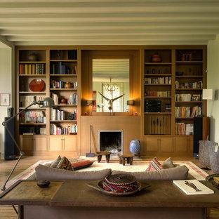 Idées déco pour un grand salon avec une bibliothèque ou un coin lecture éclectique fermé avec un sol en bois brun, une cheminée standard, un mur vert, un manteau de cheminée en bois et aucun téléviseur.