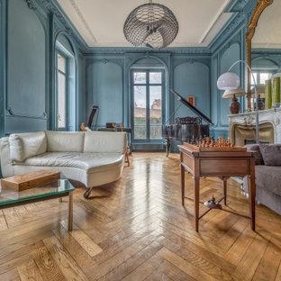 Mittelgroßes, Fernseherloses Klassisches Wohnzimmer mit blauer Wandfarbe, braunem Holzboden und Kaminumrandung aus Stein in Lyon