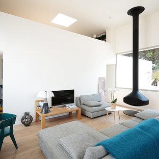 Cette photo montre un salon tendance ouvert et de taille moyenne avec un mur blanc, un sol en bois clair, un téléviseur indépendant et un poêle à bois.