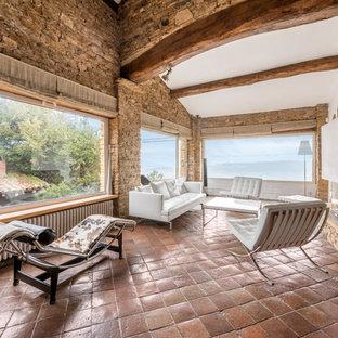 Cette photo montre un grand salon méditerranéen avec un mur beige, un sol en carreau de terre cuite, aucun téléviseur, une salle de réception et une cheminée double-face.