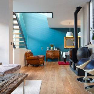 Exemple d'un salon tendance de taille moyenne et ouvert avec un mur bleu, un sol en bois clair, un poêle à bois, un manteau de cheminée en métal et un téléviseur indépendant.