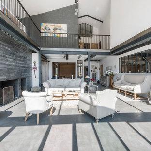 Aménagement d'un grand salon industriel ouvert avec une salle de réception, un mur blanc, béton au sol, une cheminée ribbon et aucun téléviseur.