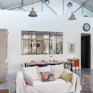 Aménagement d'un grand salon industriel ouvert avec un mur blanc, béton au sol, cheminée suspendue, un manteau de cheminée en métal et un sol gris.