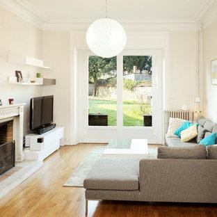 Idées déco pour un salon classique fermé et de taille moyenne avec une salle de réception, un mur beige, un sol en bois brun, une cheminée standard, un téléviseur indépendant, un sol beige et un manteau de cheminée en pierre.