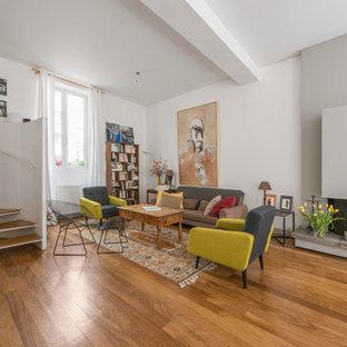 Aménagement d'un salon avec une bibliothèque ou un coin lecture contemporain de taille moyenne et ouvert avec un mur blanc, un sol en bois brun, une cheminée ribbon et aucun téléviseur.